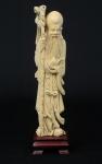 """Figura esculpida em marfim, representando """"Imortal com cajado e Pêssego"""". Base em madeira trabalhada. Alt.: 23cm. China - 1930."""