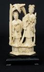 """Grupo esculpido em marfim, representando """"2 damas com cesto e peônias sob palmeira"""". base em madeira. Alt.: 19cm. China - 1900."""
