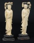 """Par de figuras esculpidas em marfim, representando """"Divindade Kuan Yin com ramos de flores"""". Alt.: 17,5cm. Base em madeira trabalhada. China - 1900."""