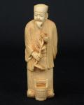 """Okimono esculpido em marfim, representando """"Camponês com girassol e tina de água aos seus pés"""". Alt.: 13cm. Assinado. Japão - 1900."""