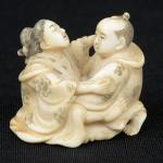 """Netsuke esculpido em marfim, representando """"Casal em cena erótica"""". Alt.: 3,3cm. Japão - 1900."""