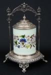"""""""Biscuit Box"""" alemão art nouveau da marca """"WMF"""" (circa 1900) em vidro opalinado esmaltado com decoração floral. Base, guarnições e tampa espessuradas a prata com decoração no estilo. Alt.: 32cm. (Pequena marca de fabricação na borda). (Em função da fragilidade, este lote só poderá ser enviado para fora do estado através de transportadora especializada)."""