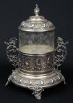 """""""Biscuit Box"""" alemão estilo barroco-rococó da marca """"WMF"""" (circa 1900) em vidro moldado com lavrados florais. Base, guarnições e tampa espessuradas a prata com decoração no estilo. Pegas no feitio de """"Fênix"""". Alt.: 28cm. (Em função da fragilidade, este lote só poderá ser enviado para fora do estado através de transportadora especializada)."""